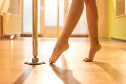 Pole dance. Slender nude female legs in dance studio at sunset.