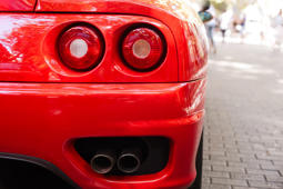 Back view of red ferrari. Exhaust and headlights
