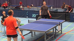 a group of people standing around a table: One of the most unbelievable ping pong shots ever
