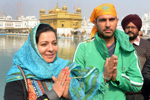 Indian international cricketer Yuvraj Singh (R) and his mother pay respects at the Sikh Shrine Golden temple in Amritsar on February 11, 2014. Singh, along with his mother, visited the city to pay their respects at the Sikh Shrine. AFP PHOTO/NARINDER NANU (Photo credit should read NARINDER NANU/AFP/Getty Images)