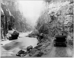 Tourists drive their car on a dirt road along Yellowstone River in the early days of Yellowstone National Park.   (Photo by Library of Congress/Corbis/VCG via Getty Images)