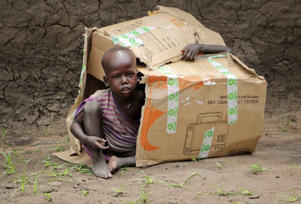 In this photo taken Friday, Aug. 17, 2018, two young boys play inside a cardboard box during an aid distribution by international humanitarian group Oxfam on the island of Nyajam, off the mainland from the opposition-held town of Nyal in Unity state, in South Sudan. The government claims a shattering five-year civil war is finally over, but skepticism soars and the latest attempt at peace already shows cracks. (AP Photo/Sam Mednick)