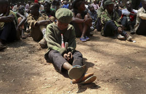 "FILE - In this Feb. 7, 2018, file photo, a young child soldier sits on the ground at a release ceremony, where he and others laid down their weapons and traded in their uniforms to return to ""normal life"", in Yambio, South Sudan. Six African nations are among the 10 worst in the world to be a child in a war zone, according to a new report by Save the Children released Thursday, Feb. 15, 2018 that looks at factors including attacks on schools, child soldier recruitment, sexual violations, killings and lack of humanitarian access. (AP Photo/Sam Mednick, File)"