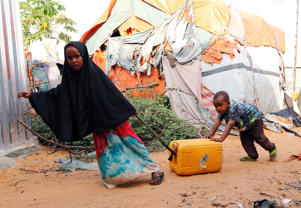 Somali children push a jerry-can of water outside their makeshift shelter at a camp for the internally displaced people outside Mogadishu, Somalia August 28, 2018 REUTERS/Feisal Omar