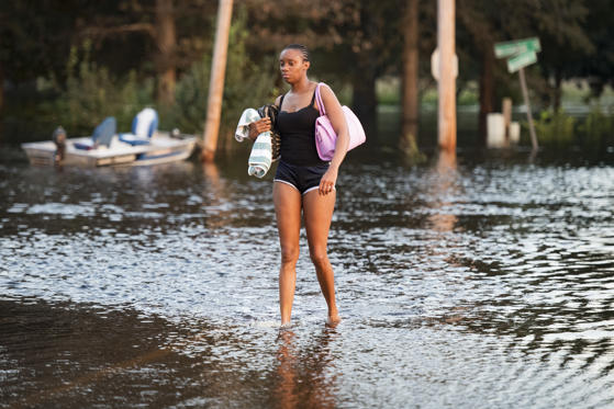 Slide 2 of 105: BUCKSPORT, SC - SEPTEMBER 26: A woman walks in  floodwaters from the Waccamaw River caused by Hurricane Florence on September 26, 2018 in Bucksport, South Carolina. Nearly two weeks after making landfall in North Carolina, river flooding continues after Florence in northeastern South Carolina. (Photo by Sean Rayford/Getty Images)