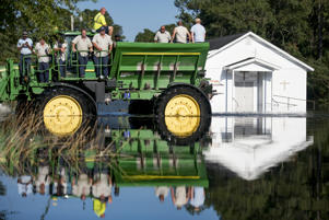 BUCKSPORT, SC - SEPTEMBER 26: Workers uses farm machinery to navigate floodwaters from the Waccamaw River caused by Hurricane Florence on September 26, 2018 in Bucksport, South Carolina. Nearly two weeks after making landfall in North Carolina, river flooding continues after Florence in northeastern South Carolina. (Photo by Sean Rayford/Getty Images)