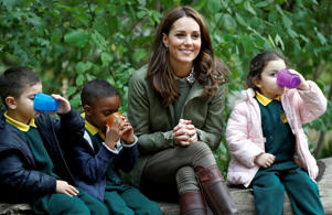 The Duchess of Cambridge sits on a log with children at Sayers Croft Forest School and Wildlife Garden at Paddington Recreation Ground, London.