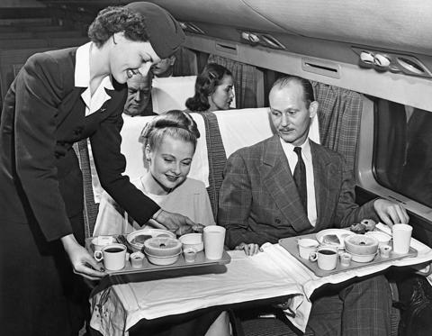 Slide 1 of 46: A stewardess serves a meal to a couple on an American Airlines flight, mid to late 1950s. (Photo by Underwood Archives/Getty Images)