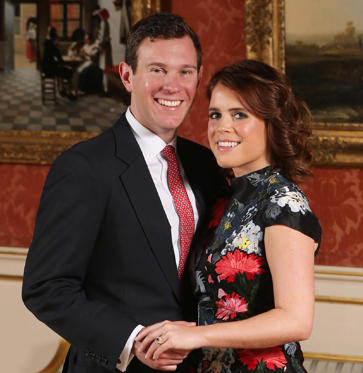 Slide 1 de 11: Britain's Princess Eugenie of York (R) poses with her fiance Jack Brooksbank in the Picture Gallery at Buckingham Palace in London on January 22, 2018, after the announcement of their engagement. Britain's Princess Eugenie of York wears a dress by Erdem, shoes by Jimmy Choo and a ring containing a padparadscha sapphire surrounded by diamonds. Britain's Princess Eugenie of York has got engaged, Buckingham Palace announced January 22, 2018, lining up a second royal wedding this year at the church where Prince Harry will tie the knot. / AFP PHOTO / POOL / Jonathan Brady (Photo credit should read JONATHAN BRADY/AFP/Getty Images)