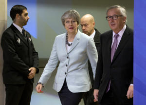 British Prime Minister Theresa May, left, walks with European Commission President Jean-Claude Juncker, right, prior to a meeting at EU headquarters in Brussels on Friday, Dec. 8, 2017. (AP Photo/Virginia Mayo)