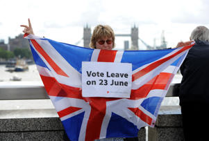 A leave supporter is seen as fishing boats campaigning for Brexit sail down the Thames through central London, United Kingdom on June 15, 2016. A Brexit flotilla of fishing boats sailed up the River Thames into London today with foghorns sounding, during a protest against EU fishing quotas by the campaign for Britain to leave the European Union.  (Photo by Kate Green/Anadolu Agency/Getty Images)