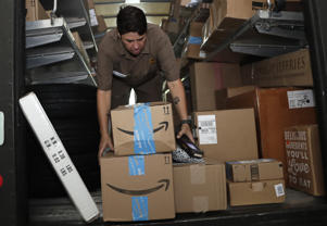 UPS employee Liz Perez unloads packages for delivery in Miami, Tuesday, July 17, 2018. Amazon Prime Day was launched July 16 and and will be six hours longer than last year's and will launch new products. (AP Photo/Lynne Sladky)