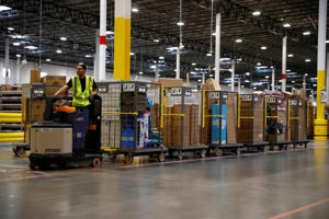 An associate uses his vehicle to pull a long line of tugs filled with goods during a tour of the Amazon fulfillment center Thursday, May 3, 2018, in Aurora, Colo. More than 1,000 full-time associates work in the Aurora facility, which opened in September 2017, and is one of more than 100 such fulfillment centers scattered across North America. (AP Photo/David Zalubowski)
