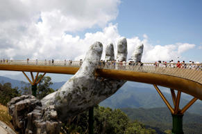 Tourists walk past giant hand structure on the Gold Bridge on Ba Na hill near Danang City, Vietnam August 1, 2018. REUTERS/Kham TPX IMAGES OF THE DAY
