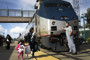 An Amtrak engineer leans on the locomotive as passengers disembark from Amtrak's California Zephyr at the end of its daily 2,438-mile trip to Emeryville/San Francisco from Chicago that took roughly 52 hours in Emeryville, California.