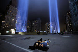 People lay and look up at the Tribute in Light installation as it is illuminated over lower Manhattan marking the 17th anniversary of the 9/11 attacks in New York City, U.S., September 11, 2018. REUTERS/Andrew Kelly