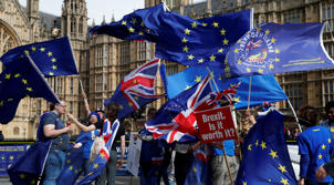 Remain supporters holds up a placards and flags of United Kingdom and the European Union outside The Palace of Westminster to show their support for 'Stopping Brexit' in London, Monday, Sept. 10, 2018. (AP Photo/Alastair Grant)