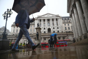 Pedestrians shelter under umbrellas in front of the Royal Exchange and the Bank of England, in London, Britain August 16, 2018.  REUTERS/ Hannah McKay