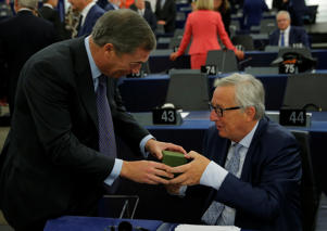 Brexit campaigner and Member of the European Parliament Nigel Farage presents a gift to European Commission President Jean-Claude Juncker before a debate on The State of the European Union at the European Parliament in Strasbourg, France, September 12, 2018.  REUTERS/Vincent Kessler