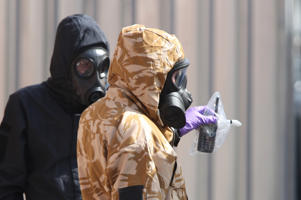Investigators in chemical suits remove an item as they work behind screens erected in Rollestone Street, Salisbury, Wiltshire, where counter-terrorism officers are investigating after a couple were left in a critical condition when they were exposed to the nerve agent Novichok.