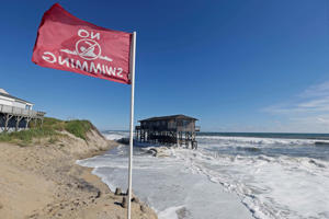 "A warning flag flies as high tide surrounds an old cottage that has already succumbed to long-term beach erosion in Nags Head, N.C., Wednesday, Sept. 12, 2018 as Hurricane Florence approaches the coast of the Carolinas. The National Weather Service says Hurricane Florence ""will likely be the storm of a lifetime for portions of the Carolina coast.""(AP Photo/Gerry Broome)"