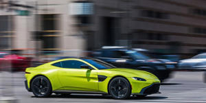 a green and yellow car in a parking lot: For years, Aston's goal with the Vantage has been to build a Porsche 911 competitor. After spending hundreds of miles in it, we can confirm that the chase is just about over.