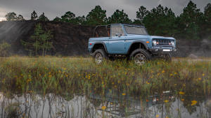 a truck is parked in front of a pond: 1973 Ford Bronco Restomod By Velocity Restorations