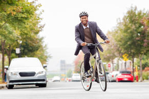 Single black male in his 30s smiling while commuting to work by bicycle