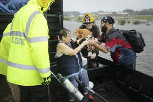 Rescue workers from Township No. 7 Fire Department and volunteers from the Civilian Crisis Response Team help rescue a woman and her dog from their flooded home during Hurricane Florence Sept. 14 in James City. Hurricane Florence made landfall in North Carolina as a Category 1 storm and flooding from the heavy rain is forcing hundreds of people to call for emergency rescues in the area around New Bern, North Carolina, which sits at the confluence of the Nueces and Trent rivers.