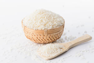 Raw rice in a bamboo basket with a rice spoon isolated on