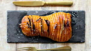 a slice of pizza sitting on top of a wooden cutting board: Hasselback butternut pumpkin recipe