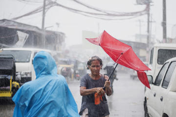 A woman holds her umbrella during heavy rains caused by Typhoon Mangkhut in Manila on September 15, 2018. - Super Typhoon Mangkhut slammed into the northern Philippines, with violent winds and torrential rains, as authorities warned millions in its path of potentially heavy destruction.