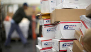 File photo of a United States Postal Service (USPS) mail clerk sorting packages at the Lincoln Park carriers annex in Chicago on Nov. 29, 2012.
