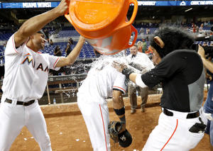 Wearing a monkey mask, Miami Marlins' Miguel Rojas, right, hits Starlin Castro, center, with a whipped cream pie as Yadiel Rivera, left, dumps water on Castro who was doing an interview after a baseball game against the Washington Nationals, Monday, Sept. 17, 2018, in Miami. (AP Photo/Wilfredo Lee)