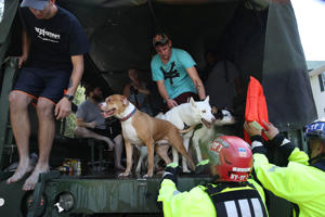 Spring Lake, NC - SEPTEMBER 18:  Tyler Bates holds his dogs as he is evacuated from his apartment by members of New York Urban Search and Rescue Task Force One due to flood waters from the Little River as it crests from the rains caused by Hurricane Florence as it passed through the area on September 18, 2018 in Spring Lake, North Carolina. The area was inundated with rain that caused concern for large scale flooding in the North Carolina and South Carolina area.  (Photo by Joe Raedle/Getty Images)