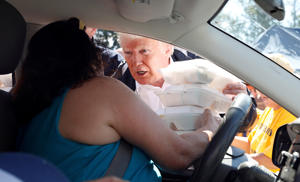 U.S. President Donald Trump hands out food through a car window while visiting a distribution center outside the Temple Baptist Church on a tour of Hurricane Florence recovery efforts in New Bern, North Carolina, U.S., September 19, 2018. REUTERS/Kevin Lamarque      TPX IMAGES OF THE DAY
