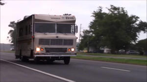 a white bus driving down a street: LS Swapped Winnebago