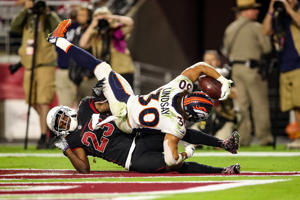 GLENDALE, AZ - OCTOBER 18: Running back Phillip Lindsay #30 of the Denver Broncos scores a 28-yard touchdown over defensive back Bene' Benwikere #23 of the Arizona Cardinals during the third quarter at State Farm Stadium on October 18, 2018 in Glendale, Arizona.