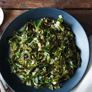a bowl of food on a plate: Collard Greens Braised in Coconut Milk