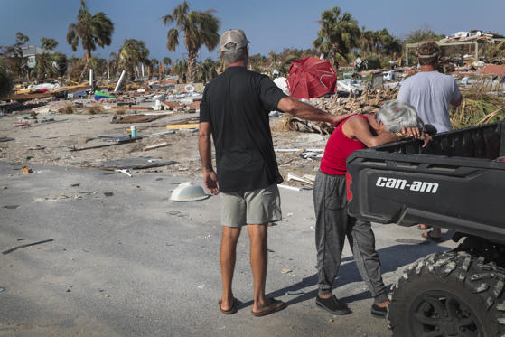 Slide 1 of 86: LeClaire Bryan (red shirt), mother of country music artist Luke Bryan, is comforted by James Whiddon after she becomes overwhelmed at the sight of her home after it was severely damaged by Hurricane Michael on October 19, 2018 in Mexico Beach, Florida. Hurricane Michael slammed into the Florida Panhandle on October 10, as a category 4 storm causing massive damage and claiming over 30 lives.