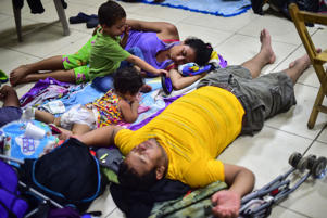 Honduran migrants heading in a caravan to the US, spend the night at a temporary shelter in Ciudad Hidalgo, Chiapas state, Mexico, on October 19, 2018. - The caravan of mainly Honduran migrants, whose journey has triggered escalating anti-immigrant rhetoric from US President Donald Trump, surged through a series of police lines and barricades up to the final fence on Mexico's southern border.