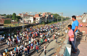 A crowd gathers at the site of Friday's train accident in Amritsar, India, Saturday, Oct. 20, 2018. A speeding train ran over a crowd watching fireworks during a religious festival in northern India on Friday evening, killing more than 50 people and injuring dozens more, police said. (AP Photo/Prabhjot Gill)