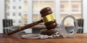 Metal police handcuffs and judge gavel on wooden desk, blur office background. 3d illustration