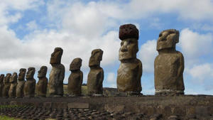 a stone building with Easter Island in the background: Researchers say they figured out how the ancient people of Easter Island put 12-ton hats on the mysterious statues.