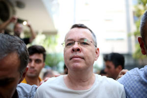 Pastor Andrew Craig Brunson (R), escorted by Turkish plain clothes police officers as he arrives at his house on July 25, 2018 in Izmir. - A Turkish court on July 25, 2018 ruled to place under house arrest an American pastor who has been imprisoned for almost two years on terror-related charges in a case that has raised tensions with the United States, state media said. The state-run Anadolu news agency said he was being put under house arrest, although it was not clear if he had already left prison. (Photo by STRINGER / AFP)        (Photo credit should read STRINGER/AFP/Getty Images)