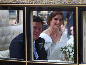 Princess Eugenie of York and her husband Jack Brooksbank leave in a carriage after their wedding ceremony.