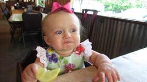 a little girl sitting at a table eating food: Adorable moment baby eats lemon for the first time