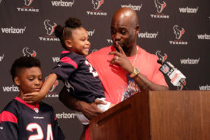 Houston Texans cornerback Johnathan Joseph, with his daughter Janae and son Jonathan Jr., talks with the media following an NFL football game against the Buffalo Bills, Sunday, Oct. 14, 2018, in Houston. (AP Photo/Michael Wyke)