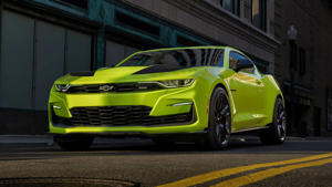 a green and yellow car in front of a building: 2019 Chevrolet Camaro Shock SEMA