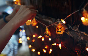 Woman hanging decorative eletric light with pumpkins. Halloween theme